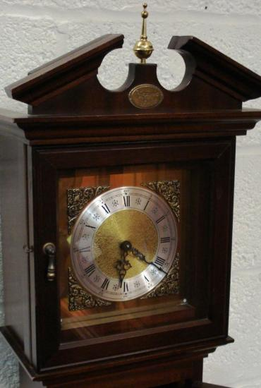 Modern mahogany finished, 8 day, weight driven striking grandfather longcase clock with German movement by Franz Hermle and Son. Decorative brass face, silvered chapter ring, brass spandrels, black hands and black roman hour markers.