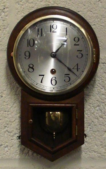 German dark oak drop dial cased wall clock by H.A.C. of Wurttemberg. Brass bezel with convex glass over a silvered dial with black arabic numerals and black painted steel hands. Separate opening window to visible brass pendulum and key holder. H.A.C. paper label on clock back with number #2609.