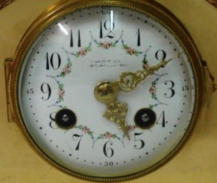 French 8 day gilt brass cased mantel clock. Gilt bezel with convex chamfered glass over white enamel dial with black arabic hour markers and ornate gold coloured hands and pretty floral  swag decoration.  Brass drum movement circa 1900, with platform lever escapement, spring driven and striking an a gong.