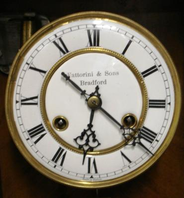 German 8 day wall clock circa 1880, spring driven pendulum movement housed in a pine case with a decorative turned finial and side columns together with applied mouldings. White enamel and brass dial with black roman hour markers and black steel hands, the dial signed 'Fattorini & Sons, Bradford' and 'Made in Baden'. The movement has a banjo style pendulum and there is an enamel pendulum regulation plate at the case bottom. Unusually the movement does not strike the hours or half hours, but plays an air on a musical box mechanism on the hour