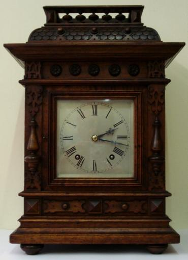 8 day Winterhalder and Hofmeier Ting Tang mantel clock circa 1900. Substantial architectural mahogany case with half turned pillars and other applied decoration throughout. Square wooden door with flat glass over heavily silvered brass dial plate with engraved black roman hours and minute track and ornate blued steel hands. Good quality square brass ting tang spring driven pendulum governed movement stamped 'D.R.Patent' (Deutsches Reich Patent) and 'W&H Sch' (Winterhalder & Hofmeier Schwarzenbach).