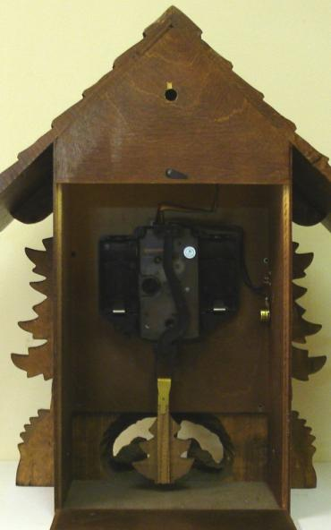 New quartz mantel / wall cuckoo clock by Harzer. Pine wood case with stylised pine tree decoration and nesting bird motif. Traditional carved light coloured wood chapter ring with roman hours and matching wooden hands. Visible pendulum and carved light wood cuckoo bird display on the hour