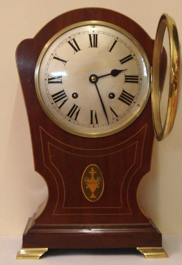 English mahogany cased 8 day bracket clock by the Astral Clock Company, circa 1920. Dome topped case with boxwood inlay and decorative marquetry plaque and gilded bracket feet. Circular gilt brass bezel with convex glass over convex silvered dial with black roman hours and black steel hands. Good quality square brass spring driven, pendulum regulated, gong striking movement with the 'Astral Coventry' back stamp and numbered #41398