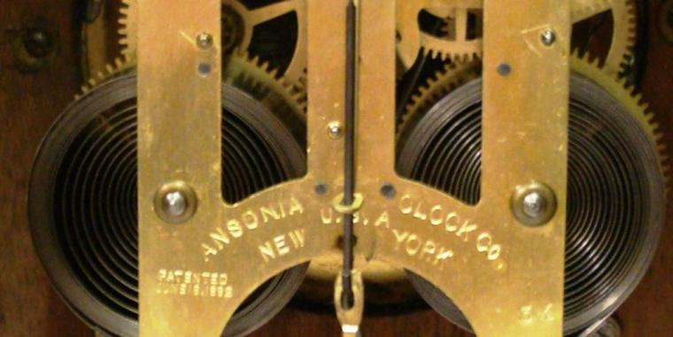 American oak cased 8 day bracket clock by the Ansonia Clock Co. circa 1900. Architectural heavily carved wooden case with turned finial and bracket feet. Circular gilt brass bezel with flat chamfered glass over matt gilt dial with slow / fast regulation at 12 o'clock with black arabic hours and ornate black steel hands. Skeleton square brass gong striking spring driven, pendulum regulated, movement stamped with 'Ansonia Clock Co, New York, USA' and 'Patented June 18,1882'.