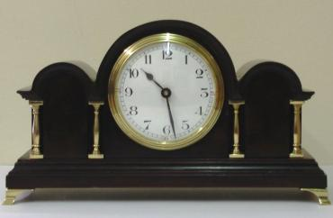 French 8 day mantel clock timepiece in an impressive triple arched dark mahogany case with gilt brass columns and bracket feet. Gilt brass bezel with convex glass over a white enamel dial with black arabic hours and black steel hands. Brass drum case movement maker unknown stamped 'France' with a good quality replacement lever escapement platform and a captive winding key.