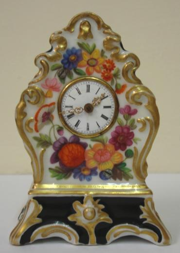 Good quality porcelain cased bedside or mantel clock with applied gilding and enamel flower decoration throughout. White enamel dial with slight damage, black roman hours and ornate gilt metal hands. Miniature brass spring driven late 19th century 8 day movement, maker unknown, with gilt  pendulum.