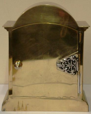 French 8 day brass cased mantel clock timepiece circa 1910. Dome topped case with decorative brass side pillars and ornate rear door hinge. Cutout brass front plate with flat glass over silvered dial plate with black roman hours and ornate black steel hands. Circular French brass drum movement, maker unknown. with lever escapement and captive winding key.