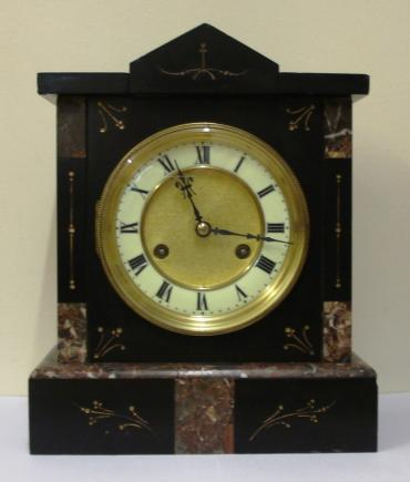 German 8 day slate and marble cased mantel clock circa 1900 by Jungans. Architectural square case with decorative engraved decoration with gilt infill. Gilt circular bezel with flat chamfered glass and white enamel chapter ring with a matt gilt interior together with black roman hours and ornate blued steel hands. Good quality spring driven, gong striking movement, regulated by a pendulum and with the Junguns touch mark.
