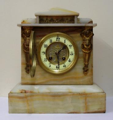 French 8 day white marble cased mantel clock circa 1890. Architectural square case with decorative applied ormolu mouldings and gilt circular bezel with flat chamfered glass over an ivory enamel chapter ring with silvered and gilt fretwork centre. Black gothic hours and ornate blued steel hands and slow / fast adjuster at 12 o/c. Good quality pendulum regulated, spring driven, gong striking French brass drum movement with an 'AD Mougin' 'Deux Medailles' touch mark and numbered #44.