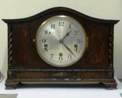 "8 day dark stained oak cased Westminster chime mantel clock circa 1920. Oblong case with wave top and integral barley twist columns and applied decorative mouldings. Circular brass bezel with convex glass over a silvered dial with black arabic hours and blued steel hands. Square brass spring driven, rod striking movement with decorative wriggle work back plate, stamped #2113, and a vertically mounted French lever escapement.  Dimensions: Height - 10"", width - 13.75"", depth - 8.25""."