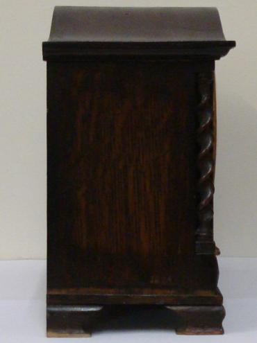 8 day dark stained oak cased Westminster chime mantel clock circa 1920. Oblong case with wave top and integral barley twist columns and applied decorative mouldings. Circular brass bezel with convex glass over a silvered dial with black arabic hours and blued steel hands. Square brass spring driven, rod striking movement with decorative wriggle work back plate, stamped #2113, and a vertically mounted French lever escapement.