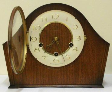 English 8 day oak veneer cased mantel clock circa 1950 by Smiths. Angular round topped case with delicate side moulding and a circular brass bezel with convex glass over an ivory coloured chapter ring. Gilt arabic hours and fretwork hands and Chime / Silent control at 9 o/c. Good quality pendulum regulated, spring driven, rod striking brass movement with decorative engine turning and stamped '-Smiths-, Made in Great Britain, Smiths English Clocks Ltd.'.