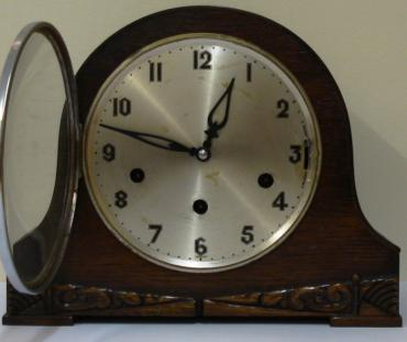 German 8 day oak veneer cased triple chime mantel clock circa 1930. Round topped hump back case with decorative front moulding and a circular chrome bezel with convex glass over a silvered dial. Black arabic hours and fretwork hands and Chime Selection (Westminster, Whittington or St.Michael) / Silent control at 3 o/c. Good quality pendulum regulated, spring driven, rod striking brass movement  stamped 'Patent No 421434, Other Patents Pending' and 'Foreign'.