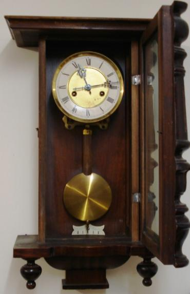 Clock for sale for restoration:- Vienna Regulator style stained pine cased gong striking wall clock by H.A.C. Flat top pediment, full length door with turned side columns, original glass over white dial with black roman hours, ornate blued steel hands. Standard brass spring driven pendulum regulated 8 day movement circa 1900. Back plate displays the H.A.C. crossed arrows mark. Lacks crest and some finials.