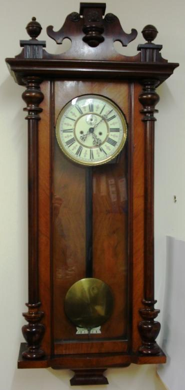 Clock for sale for restoration:- Vienna Regulator style mahogany and walnut cased gong striking wall clock by the Regulatorfabrik Germania Co. Crested pediment full length door with turned side columns, original glass over white enamel dial with black roman hours, ornate blued steel hands and subsidiary seconds dial. Good quality brass 'A' frame weight driven pendulum regulated 8 day movement circa 1880. Back plate displays the Regulatorfabrik Germania mark and is numbered #228746. Lacks some finials, weights and one weight pulley.