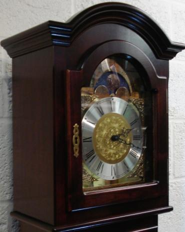 New German dark mahogany effect cased 8 day, weight driven, pendulum regulated Westminster chime grandfather longcase clock by Kieninger for Interclock. Round top hood with decorative brass face, with applied brass spandrels, and moon phase dial with silver chapter ring, black hands and black roman hour markers. Silent / Night Off / Strike selection lever at 3 o'clock.