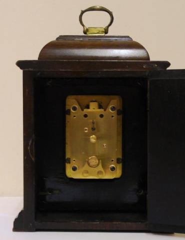 English 8 day dark stained wood cased mantel clock timepiece circa 1950 by Davall. Brass handled caddy topped case with cutout front over flat glass and silvered chapter ring with matt centre and gilt spandrels and Thwaites and Reed plaque at 6 o'clock. Black roman hours with outer arabic minutes track and black steel hands. Davall good quality brass plate movement stamped 'Made in England', with lever escapement, time change control and captive winding key.