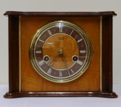 English Smiths Enfield 8 day wood veneer cased gong strike mantel clock circa 1950. Unusually shaped flat top case with gilt bezel and domed glass over a dark brown chapter ring with white roman hours and pierced gilt hands. Rear door to brass spring driven, floating balance movement with slow / fast regulation.