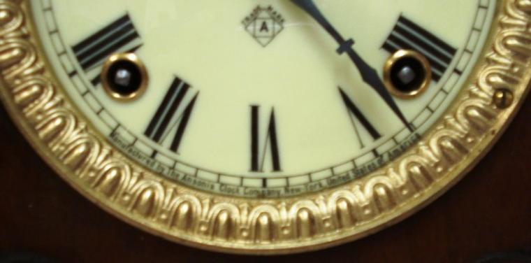 American Ansonia Clock Company 'Sharon' 8 day mahogany veneer pine cased gong strike mantel clock circa 1890. Decorative architectural case with carved and applied moulding and ornate gilt bezel with flat, chamfered glass over an ivory coloured dial with black roman hours and blued steel hands with a slow / fast adjuster at 12 o/c. Good quality brass, spring powered, pendulum driven movement stamped for the Ansonia Clock Co. and displaying a patent date of June 18, 1882.