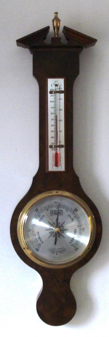 Modern Comitti of London compensated barometer in a walnut veneer case with brass finial. Circular gilt brass bezel over a silvered dial with black painted dual pressure index and a separate alcohol Centigrade and Fahrenheit thermometer.