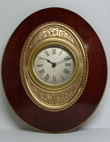 Late Victorian 8 day Straddle clock marked 'Harris, Queen's Square, Bath'. Silvered dial with black roman numerals and blued steel hands within an ornate gilded and engraved mask and  a mahogany frame.