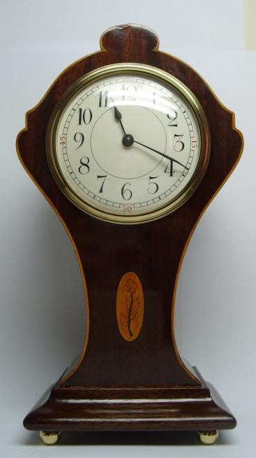 French 8 day mantel clock plain white enamelled dial arabic hour markers housed in a mahogany case with boxwood stringing and delicate marquetry inlay.