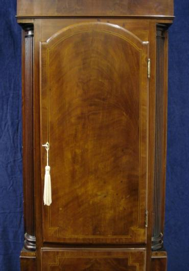 Flame mahogany and boxwood inlay cased longcase clock, with painted face and swan neck hood with fluted pillars.  Bell striking, 8 day movement, with seconds indication and date display, together with 'strike / silent' capability.   Dial signed W. HERBERT, LUDLOW