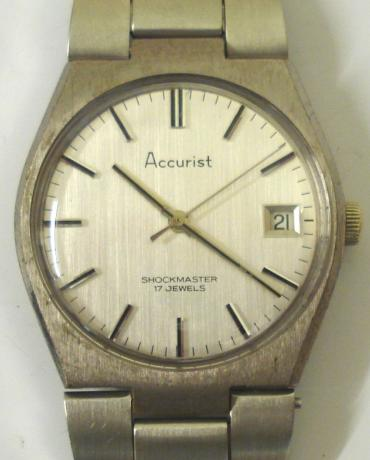Accurist Shockmaster manual wind wrist watch in a base metal case with stainless steel back and integral s/steel bracelet. Brushed silver dial with silver and black baton hour markers and matching hands with sweep seconds hand and date display at 3 o/c. Signed Accurist Swiss 17 jewel movement with screw on case back.