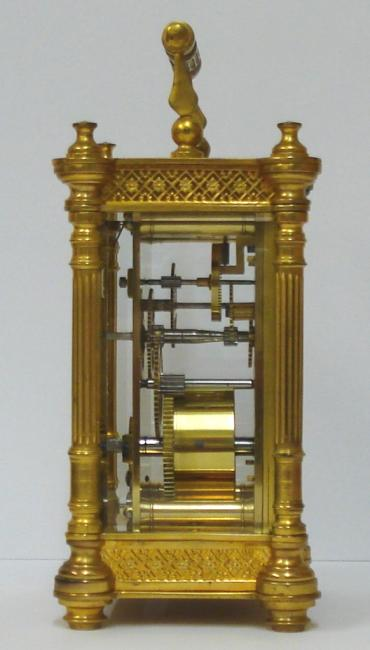 French gilt brass and 5 glass, 8 day carriage clock time piece circa 1900, maker unknown. Ornate casework with Corinthian style columns and matching carrying handle, together with open fretwork panels at top and bottom on each side. Chamfered glass panels throughout and gilt matt mask to the circular ivorine dial which has black Gothic hours and blued steel hands and a central gilt disk. Plain unmarked brass movement with contemporary cylinder escapement.