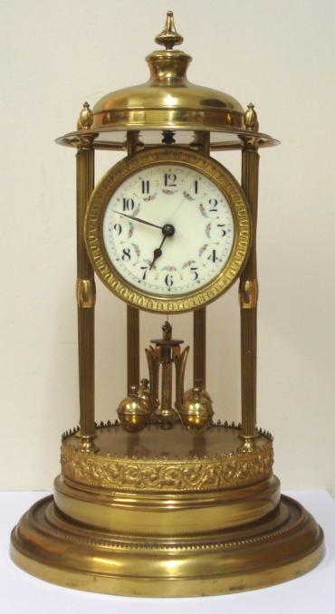 German 400 day Anniversary time piece circa 1920, maker unknown. Impressive brass dome over six  fluted support columns to ornate stepped brass base, with supported circular dial and movement. Gilt sunburst bezel with decorative enamel dial with floral swags and black arabic hours and matching hands. Standard 'anniversary' going movement with suspended oscillating slow / fast adjustable pendulum.