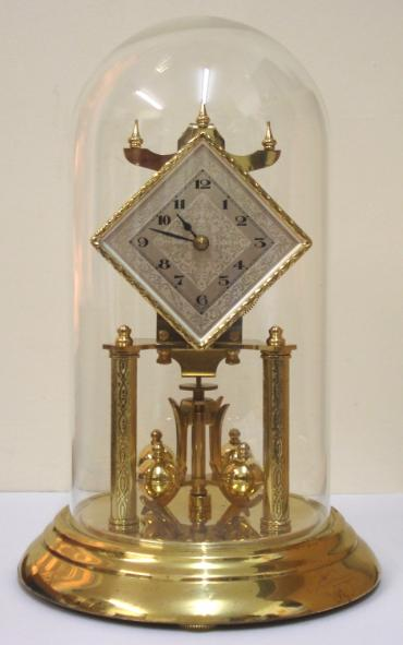 German 400 day Anniversary time piece maker unknown. Glass dome over triple stepped, level adjustment base with two engraved movement support columns. Diamond shaped gilt bezel over silvered engine turned dial plate with black arabic hours and matching black  hands. Standard brass 'anniversary' going movement with suspended oscillating slow / fast adjustable pendulum and base located locking mechanism for transportation.