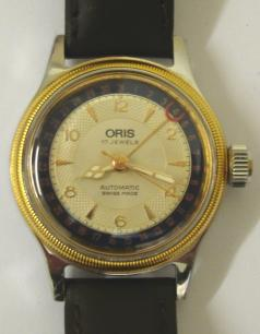 Oris 7400 BC All Stainless Steel mid size automatic wrist watch in a stainless steel case on a brown leather strap with gilt buckle. Gold plated bezel above a silvered dial with gilt baton and arabic hour markers and matching gilt luminous insert hands with sweep seconds hand. Red tipped date pointer hand indicating on an outer dark blue date track. Swiss made Oris 574 17 jewel incabloc movement with screw on case back, water resistant to 3 bar / 30 metres.