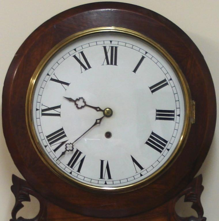 "American Ansonia Clock Co. round faced extended drop dial 8 day wall clock in a carved and moulded mahogany case with scroll bottom. Brass bezel with flat glass over a white painted dial with black roman numerals and ornate black painted hands with separate lower in view brass pendulum window. Spring driven, pendulum regulated, time piece movement, circa 1890.  Dimensions: Height - 31"", Width - 16.5"", Depth 4.5""."