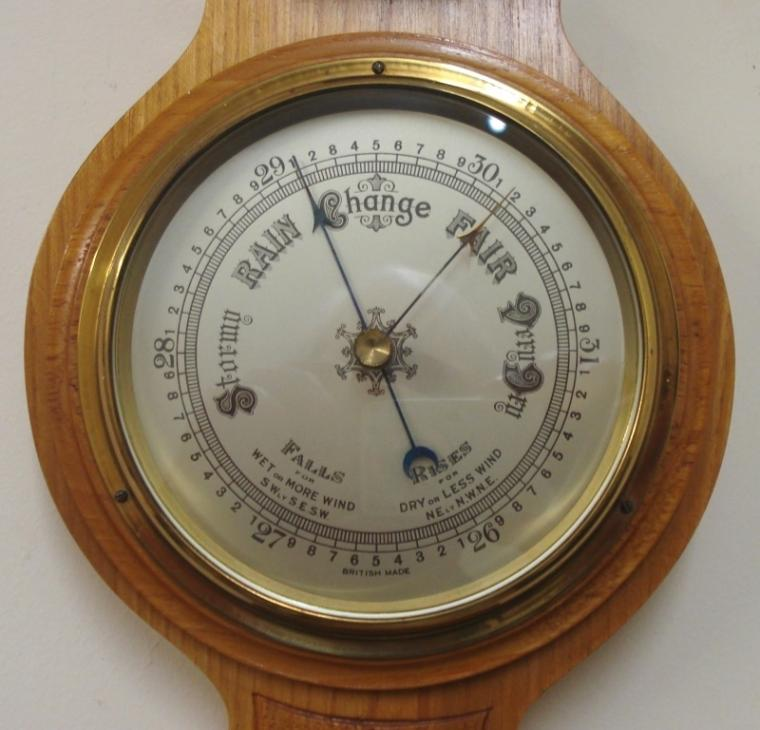 "British aneroid barometer in a light oak solid wood carved and moulded case circa 1930s. Circular brass bezel with chamfered glass over a silvered dial with black painted pressure index, blued steel pressure indicator and brass history pointer. Separate red alcohol Fahrenheit and Centigrade thermometer.  Dimensions: - Height 22.5"", width 7"", depth 2.5""."