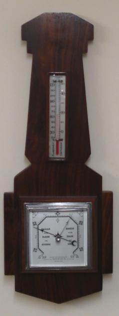"British dark walnut solid wood aneroid barometer circa 1920. Square chromed bezel with flat chamfered glass over a silvered dial with black painted pressure index, blued steel pressure indicator and silvered history pointer. Separate red alcohol Fahrenheit and Centigrade thermometer.  Dimensions: - Height 20"", width 7.5"", depth 2.5""."