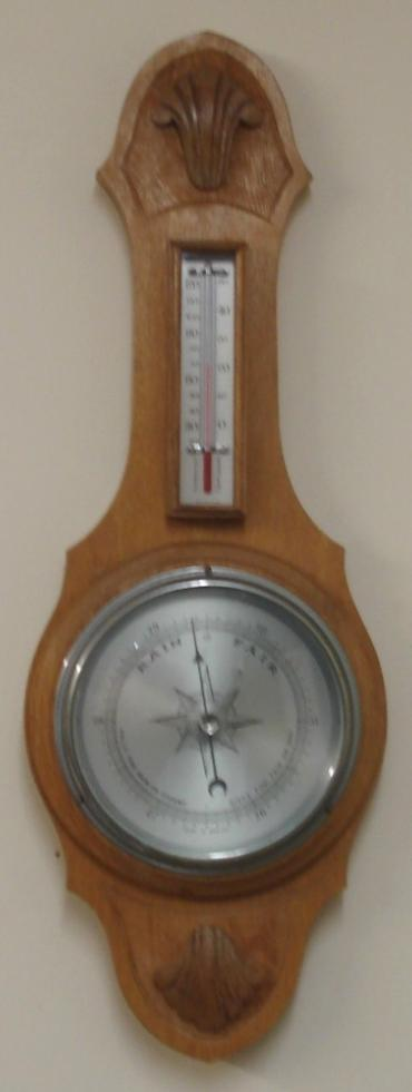 "English aneroid barometer in a light oak solid wood carved and moulded case circa 1930s. Circular chromed bezel with chamfered glass over a silvered dial with black painted pressure index, blued steel pressure indicator and silvered history pointer. Separate red alcohol Fahrenheit and Centigrade thermometer.  Dimensions: - Height 19.5"", width 7"", depth 3""."