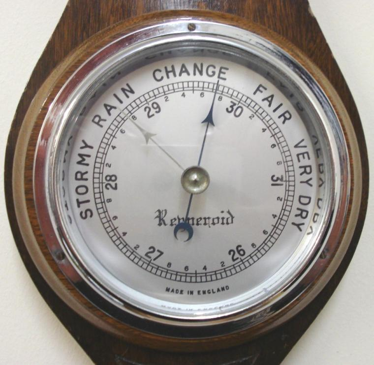 "English aneroid barometer in a dark stained oak solid wood carved and moulded case by Renneroid circa 1930. Circular chromed bezel with chamfered glass over a silvered dial with black painted pressure index, blued steel pressure indicator and silvered history pointer. Separate mercury Fahrenheit and Centigrade thermometer.  Dimensions: - Height 18.5"", width 5.5"", depth 3""."