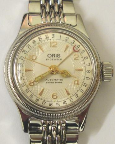 Oris 7464 BC Ladies automatic wrist watch in a stainless steel case with integral stainless steel bracelet. Silvered dial with gilt hour markers and an outer date track and gilt luminous insert hands, matching sweep seconds and red tipped date pointer. Oris 574 17 jewel automatic incabloc movement with screw-on case back water resistant to 30m.