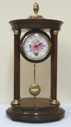 "German 8 day Portico time piece by the H.A.C. clock company of Wurttemberg circa 1900. Impressive brass finial topped dark stained wooden casework with turned support pillars and brass end pieces on a circular base with bun feet. Gilt brass bezel with convex glass over a floral decorated dial with arabic hours and black hands. Unmarked drum shaped brass spring driven pendulum regulated movement.  Dimensions: Height - 13"", Width - 6.5"", Depth - 6.5""."