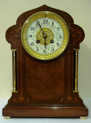 French late c19th Japy Freres mahogany cased bell strike 8 day mantel clock with onion style top and brass decorative columns and bun feet. The clock front features ornate inlaid panel work, marquetry and  edge stringing, and displays via an ornate white enamel with black arabic numerals and gilded mask and gilded surround.