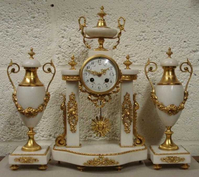 "French 8 day bell striking white marble clock garniture circa 1880, maker unknown. Classically styled in ornate ormolu decorated white marble with two lidded urns and central column supported drum case clock. Gilded bezel with concave chamfered glass over a white enamel dial with black Arabic hours and floral swags, gilded hands and two winding squares with slow/fast regulator at 12 o/c. Good quality brass drum shaped spring driven, pendulum regulated movement striking on a silvered bell and numbered #3790.  Clock Dimensions - Height 17"", Width 10"", Depth 5""."