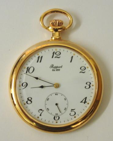 New gold plated open face pocket watch by the Rapport Company with paperwork and box. Top wind and time change 17 jewel mechanical movement with white dial, black roman hour markers, black painted hands and a subsidiary seconds dial.