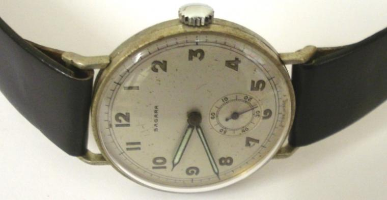 Swiss Sagara manual wind wrist watch on a black leather strap with silver buckle. Base metal case with stainless steel back numbered #316312 with silvered dial. Arabic hour markers with black luminous insert steel hands and subsidiary seconds dial. Swiss 15 jewel jewelled lever movement c1960.