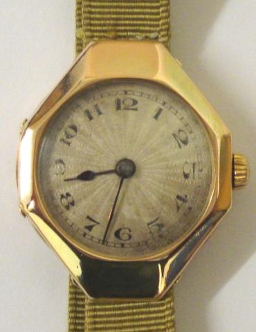 Ladies vintage Rolex manual wind wrist watch in an octagonal 9ct gold case on a gold coloured fabric strap with gilt fastening. Silvered radial dial with black Arabic hour markers and blued steel hands. Signed Rolex jewelled lever movement with Rolex case numbered #1158006 and import hallmarked for London circa 1921.