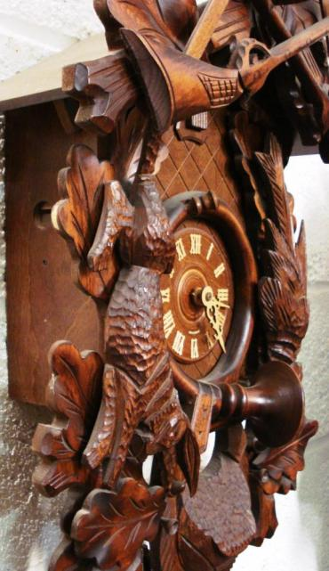 New 2 weight driven 8 day duration cuckoo clock with cuckoo displaying on the hour and half hour and striking on a gong. Elaborate carved case with hunting themes and leaf pendulum, and stag's head finial.
