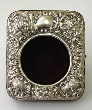 Silver fronted red leather watch stand sized for a Goliath pocket watch with back strut and dark red plush velvet interior. Highly embossed silver  front hallmarked for Birmingham, 1909, maker S*B (Synyer & Beddoes).