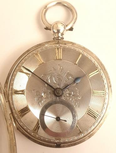 English silver cased key wound fusee lever pocket watch with London hallmark for circa 1850. Silver engine turned and floral engraved dial with gilt Roman hours and blued steel spade hands with subsidiary seconds dial at 6 o/c. Decoratively engraved cock piece with diamond end stone and unsigned back plate numbered #11091 with the number repeated on the case interior.