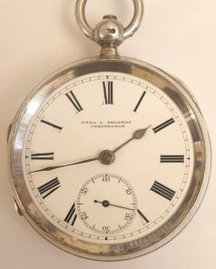 English silver cased pocket watch manufactured by Newsome and Co. and retailed by Ezra L.Feldman of Cheltenham. Key wind and time change with white enamel dial and black Roman hours with gilt spear and shaft hands and subsidiary seconds dial, the silver case hallmarked for London circa 1888. Fusee movement with floral decorated cock piece and jewelled end stone signed for Ezra Feldman and stamped for Newsome and Co. beneath the dial plate with #98303 numbering throughout.
