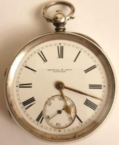 English silver cased pocket watch by Kendal & Dent, London in a case bearing a Birmingham hallmark for circa 1896. Key wind and time change with signed white enamel dial and black Roman hours with gilt hands and subsidiary seconds dial. Signed going barrel movement with floral decorated cock piece and jewelled end stone and with inscription '106 Cheapside, London' and numbered #82226, the number repeated on the case back with the 'K&D' stamp.