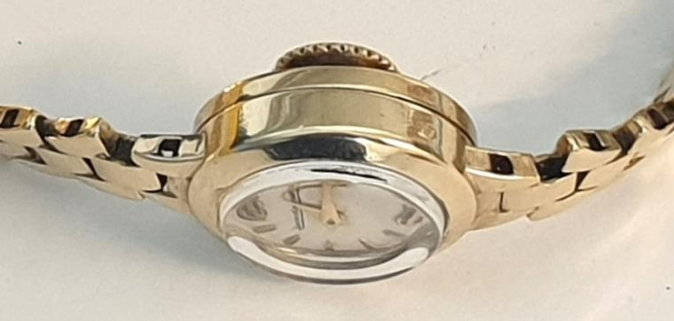 Ladies Swiss Jaegar LeCoultre manual wind wrist watch in a 9ct gold case with integral 9ct gold bracelet hallmarked for London circa 1961. Signed silvered dial with gilt hour markers and matching gilt hands. Signed jewelled lever movement numbered #49836 with back wind and time change function.